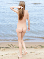 Fascinating long haired teen bombshell showing her superior shapely body on the seaside.